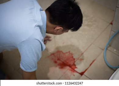 Young asian man vomiting blood in the bathroom