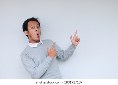 Young asian man waer white shirt is surprised and shouting wow with pointing right with his finger isolated on gray background with copy space fot your text.