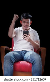 young asian man watching to smart phone screen cheer up something with exciting emotion