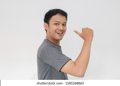 Young Asian man wear grey shirt with happy smiling face and thumbs up