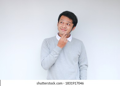 Young Asian man wear grey shirt with thinking and looking idea gesture