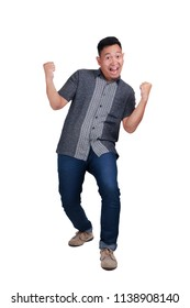 Young Asian man wearing batik shirt and jeans smilling and showing winning victory gesture. Success people raising his fists up. Isolated on white. Full body portrait.