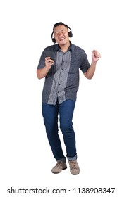Young Asian man wearing blue jeans and batik shirt listening to music and dancing happily. Isolated on white. Full body portrait