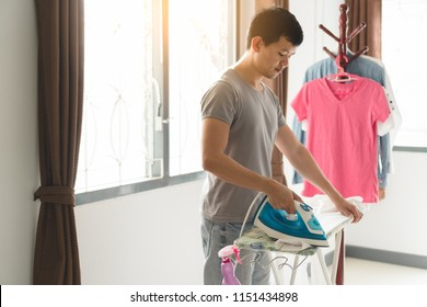 Young asian man wearing gray t-shirt ironing white clothes on iron board with steaming blue iron at home. Man in role of a woman duty. Housework and household concept.