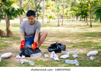 Young Asian man wearing orange gloves and collecting trash in garbage bag in the park. Save the earth and environmental concern concept