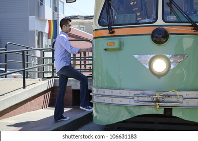 Young Asian man wearing a shirt and jeans steps up onto a tram car