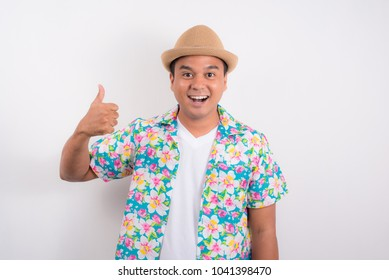 Young asian man wearing summer shirt and showing thumb up for Songkran festival in Thailand.