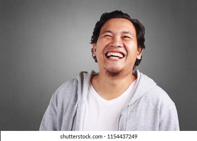 Young Asian man wearing white shirt and gray jacket laughing hard expression.  Background on gray. Close up head and shoulder