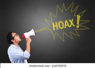 Young Asian man wearing white and blue shirt shouting using megaphone, angry expression. Close up body portrait. With a hoax sign