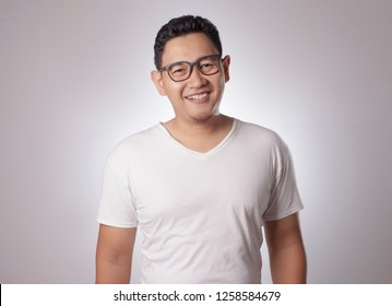 Young Asian man wearing white shirt , smiling happily expression.  Background on gray. Close up head and shoulder