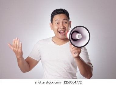 Young Asian man wearing white shirt advertisement concept, Smiling expression using megaphone. Close up body portrait over grey background