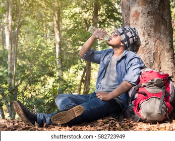 Young asian man wears jeans(hipster style) with backpack sitting and drinking water at tree in nature forest during trekking/hiking/traveling on vacation/holiday, freedom lifestyle outdoor concept