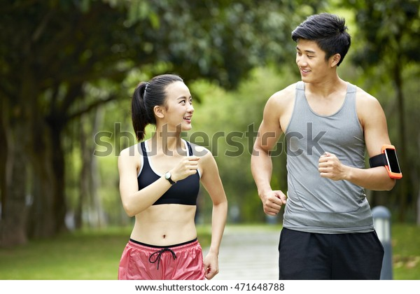 young asian man and woman couple running jogging and talking in a city park.