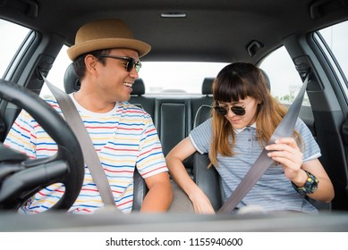 Young asian man and woman putting on his seat belt in his car. Safety drive concept.