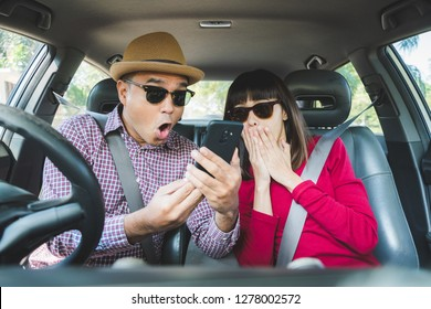 Young asian man and woman shocked when see the smartphone while sitting in car.