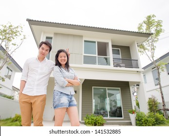 Young asian man and woman standing in front of a new house