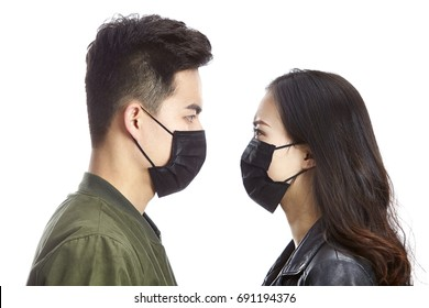 young asian man and woman wearing black mask staring at each other, isolated on white background.