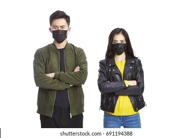 young asian man and woman wearing black mask looking at camera frowning, isolated on white background.