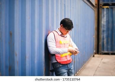 Young Asian man worker looking at smartphone. Check and control loading freight logistic Containers at commercial shipping dock smiling felling good and happy. Cargo freight ship import export concept