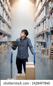 Young Asian man worker with shopping cart doing stocktaking of product in cardboard box on shelves in warehouse by using digital tablet. Physical inventory count concept