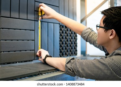 Young Asian man worker using tape measure for measuring dimension of wooden floor pavement block pattern mockup. Shopping lifestyle in warehouse concept