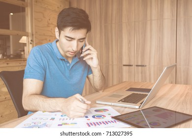 Young asian man working in his office.