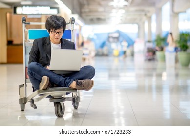 Young asian man working on airport trolley with his laptop computer during waiting for a connecting flight, freelance lifestyle and digital nomad concepts