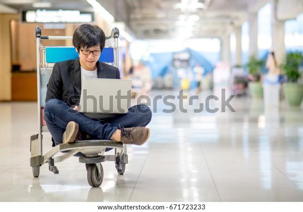 Joven asiático trabajando en el tranvía del aeropuerto con su computadora portátil durante la espera de un vuelo de conexión, estilo de vida independiente y conceptos de nómada digital