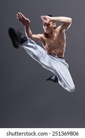 Young asian man workout over grey background karate jump kick