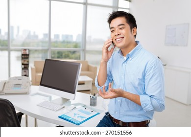 Young Asian manager standing at his workplace and calling on the phone