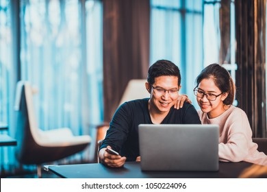 Young Asian married couple working together using laptop at home or modern office with copy space. Startup family business, SME entrepreneur, business partner, love relationship, or freelance concept