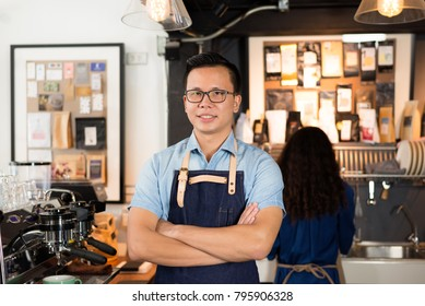 Young asian men barista smiling at coffee shop counter background, start up small business owner food and drink concept.