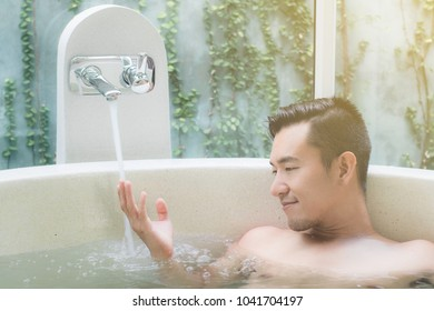 young asian men touch water in bathtub