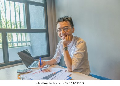 Young Asian millennial sitting at working desk next to window