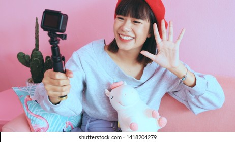 Young asian millennial woman taking selfie and live streaming at the cafe, lifestyle and technology concept