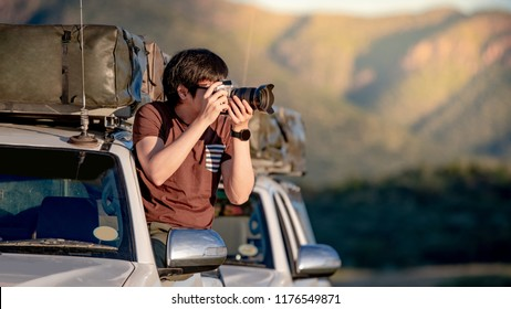 Young Asian mle traveler and photographer sitting on the car window taking photo on road trip in Namibia, Africa. Travel photography concept