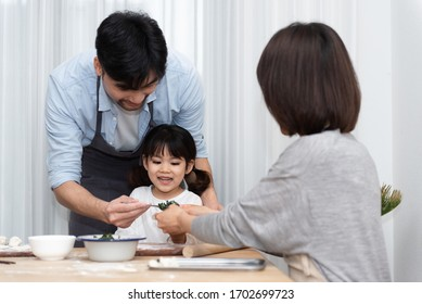 Young Asian mom and dad making dumplings with daughter