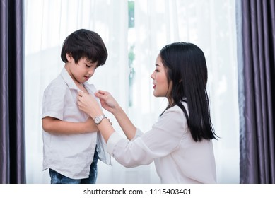 Young Asian mom dressed up son outfits for preparing go to school. Mother and son concept. Happy family and Home sweet home theme. Preschool and Back to school theme.
