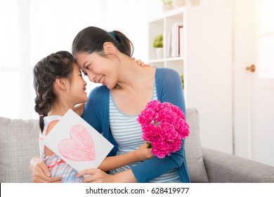 young asian mother accepting the little daughter hand painted card, embracing, little girl holding a pink flower girl, sitting on the sofa in the living room, happy looking at each other, copy space for mother's day.