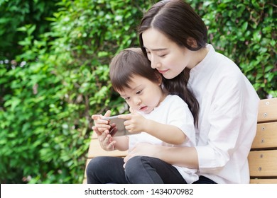 young asian mother and child using smart phone in park