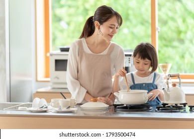 young asian mother and daughter cooking at kitchen