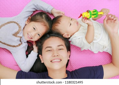 Young Asian mother daughter and son lying on pink mattress mat looking at camera.