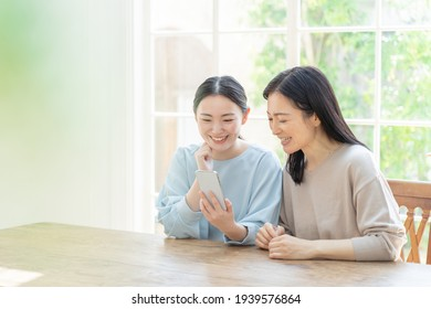 young asian mother and daughter using smart phone in the living room