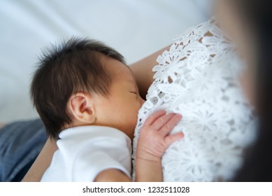 Young Asian mother holding her newborn child while breastfeeding child on the bed. She is looking her baby with love. Seen from top view. Mother's breastfeeding concept.