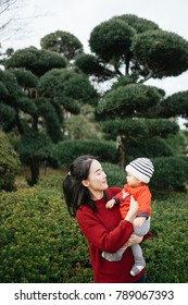 Young asian mother holding and kissing her baby boy child.Mom nursing baby.Woman and baby boy relax in japan garden in Japan.Relationship Family and Mother day concept.