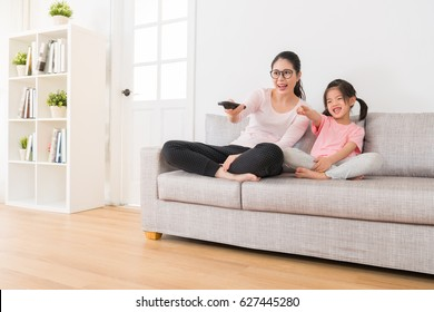 young asian mother holding a remote control sitting on the couch with a lovely daughter pointing to TV happy to pick the funny channel at the holiday leisure family time.