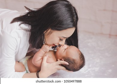 Young Asian mother hugging, kissing newborn child. Mom gently care nursing baby boy on bed infant nursery. Parent and little kid relaxing. Family playing together. Love, trust and tenderness concept.