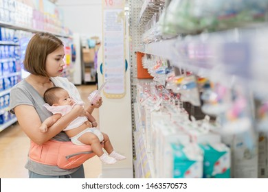 Young asian mother and little cute baby in carrier are shopping newborn baby product in supermarket. Mom is choosing new nipple for her child.