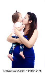 Young asian mother is pregnant hugging kid in the arms and kiss lip her daughter, on white background with family concept