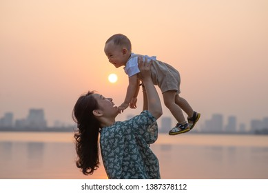 Young asian mother raise her son in beautiful sunset
